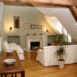 パリの中くらいのトラディショナルスタイルのおしゃれなLDK (緑の壁、無垢フローリング、標準型暖炉、石材の暖炉まわり、テレビなし) の写真