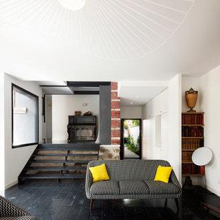 Cette image montre un salon design fermé et de taille moyenne avec un mur blanc, aucune cheminée, une salle de musique, aucun téléviseur et un mur en pierre.