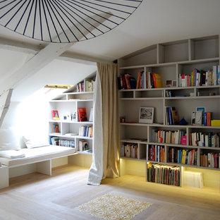 Idée de décoration pour un salon design avec un mur beige et un sol en bois clair.
