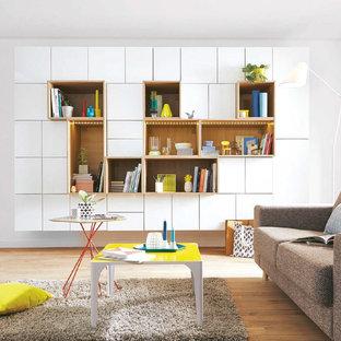 Cette image montre un salon avec une bibliothèque ou un coin lecture minimaliste de taille moyenne et ouvert avec un mur blanc, un sol en bois brun, aucune cheminée et aucun téléviseur.