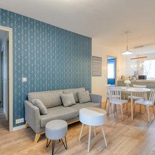 Modelo de salón abierto, actual, de tamaño medio, con paredes azules, suelo de madera clara y suelo rosa