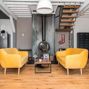 Idées déco pour un salon industriel ouvert avec un mur gris, un sol en bois brun et cheminée suspendue.