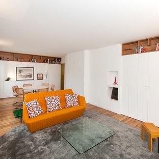 Idée de décoration pour un salon design ouvert avec un mur blanc, un sol en bois brun et un sol marron.