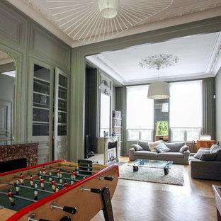 Idée de décoration pour un salon tradition de taille moyenne et ouvert avec une salle de réception, un mur vert, un sol en bois clair, une cheminée standard et un téléviseur indépendant.