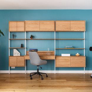 Idées déco pour un salon contemporain avec un mur bleu, un sol en bois brun, un téléviseur indépendant et un sol marron.