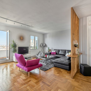 Exemple d'un salon tendance avec un mur gris, un sol en bois brun, un téléviseur indépendant et un sol marron.