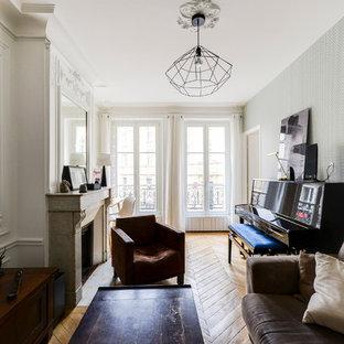 Inspiration pour un salon traditionnel de taille moyenne et fermé avec un mur blanc, un sol en bois clair, une cheminée standard, un téléviseur fixé au mur, un sol marron et un manteau de cheminée en pierre.