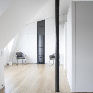 Réalisation d'un salon design ouvert avec un mur blanc, un sol en bois clair, un poêle à bois, un manteau de cheminée en métal et un téléviseur dissimulé.