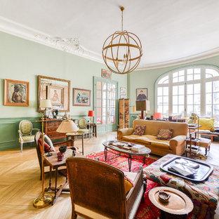Cette image montre un salon traditionnel avec un mur vert, un sol en bois clair, une cheminée standard, un manteau de cheminée en pierre et un sol marron.