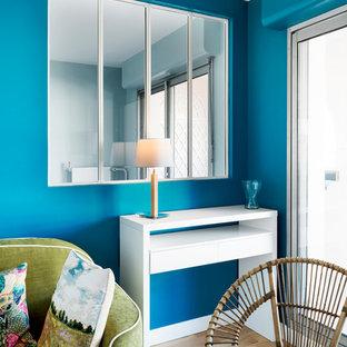Immagine di un soggiorno nordico di medie dimensioni e chiuso con pareti blu, pavimento in compensato, nessun camino e pavimento beige