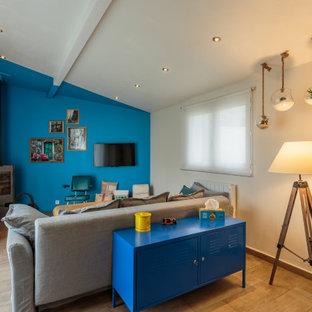 Idées déco pour un salon éclectique ouvert avec un mur bleu, un poêle à bois, un sol marron, un sol en bois clair et un téléviseur fixé au mur.