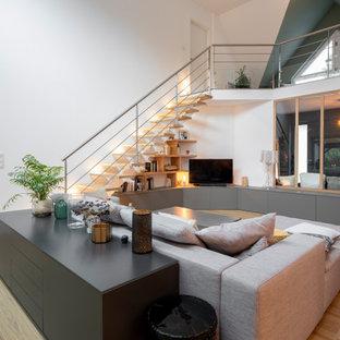 Cette photo montre un grand salon tendance ouvert avec un mur blanc, un sol en bois clair, un téléviseur indépendant et un sol beige.