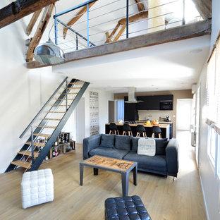 Exemple d'un grand salon industriel ouvert avec un mur blanc, un sol en bois clair, aucune cheminée et aucun téléviseur.