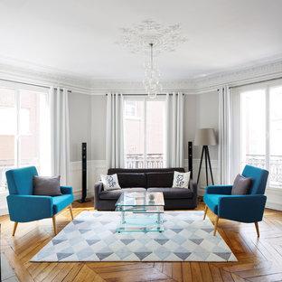 Idée de décoration pour un salon tradition de taille moyenne et ouvert avec une salle de réception, un mur gris et un sol en bois brun.