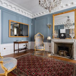 Réalisation d'un grand salon victorien fermé avec un mur bleu, un sol en bois foncé, une cheminée standard, un téléviseur fixé au mur, un sol marron et boiseries.