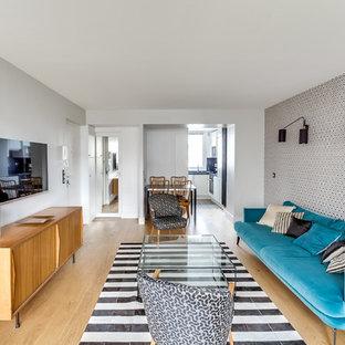 Aménagement d'un petit salon rétro ouvert avec un téléviseur fixé au mur, un mur blanc, un sol en bois clair, aucune cheminée et un sol marron.