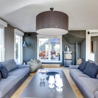 Imagen de salón abierto, minimalista, grande, con paredes grises, suelo de madera clara, estufa de leña, televisor independiente, suelo marrón y marco de chimenea de metal