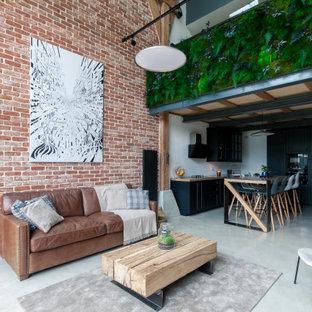 Réalisation d'un grand salon urbain ouvert avec un mur rouge et un sol gris.