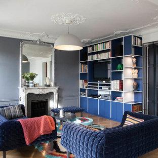 Cette photo montre un grand salon chic avec un mur gris, un sol en bois brun, une cheminée standard, un téléviseur fixé au mur et un sol marron.