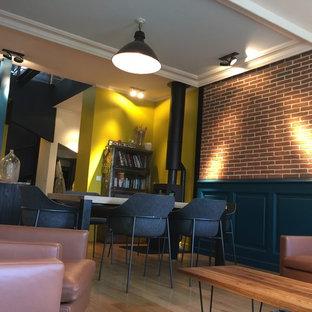 Imagen de salón abierto, urbano, grande, con paredes multicolor, suelo de madera clara, estufa de leña y suelo beige