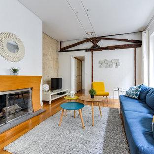 Cette image montre un salon rustique avec un mur blanc, un sol en bois clair, une cheminée standard, un manteau de cheminée en bois, un téléviseur indépendant et un sol marron.