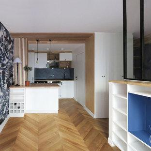 Immagine di un piccolo soggiorno minimal aperto con angolo bar, pareti bianche, parquet chiaro, nessun camino, TV autoportante e pavimento beige