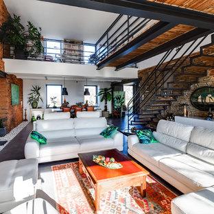 Esempio di un ampio soggiorno bohémian aperto con sala formale, pareti rosse, pavimento in cemento, nessun camino, TV a parete e pavimento grigio
