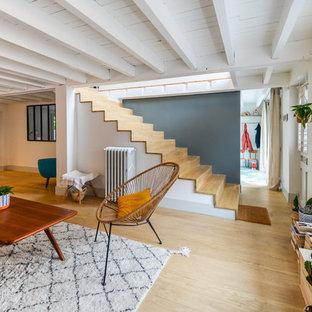 Diseño de salón para visitas abierto, contemporáneo, extra grande, sin televisor, con suelo de madera clara, suelo beige, paredes grises y estufa de leña