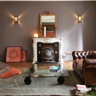 Inspiration pour un salon bohème de taille moyenne et fermé avec un mur gris, un sol en bois brun, une cheminée standard, un manteau de cheminée en pierre et aucun téléviseur.