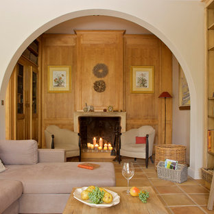 Inspiration for a large timeless open concept terra-cotta floor living room library remodel in Marseille with beige walls, a standard fireplace and no tv