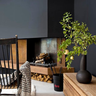 Mid-sized contemporary open concept living room in Montpellier with black walls, concrete floors, a standard fireplace and no tv.