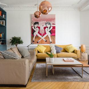 Réalisation d'un salon design avec un mur blanc, un sol en bois clair, un sol beige et boiseries.