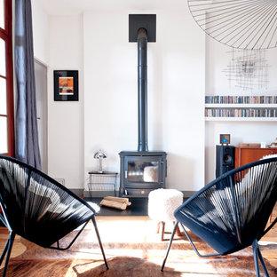 Exemple d'un grand salon scandinave ouvert avec un mur blanc, un sol en bois brun, un poêle à bois et aucun téléviseur.