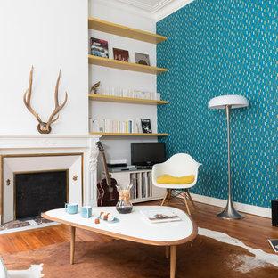 Immagine di un soggiorno nordico di medie dimensioni e chiuso con pareti blu, pavimento in legno massello medio, camino classico, cornice del camino in intonaco e TV autoportante