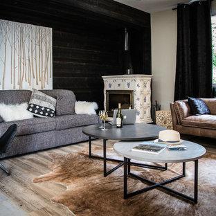 Cette image montre un salon chalet avec un mur noir, un sol en bois clair, une cheminée d'angle, un manteau de cheminée en carrelage et un sol beige.