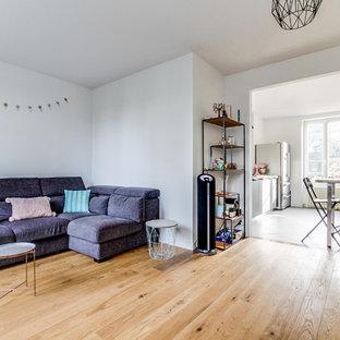 Esempio di un soggiorno scandinavo di medie dimensioni e aperto con pareti bianche, pavimento in compensato e camino ad angolo