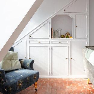 Imagen de salón cerrado, minimalista, de tamaño medio, sin chimenea, con paredes blancas, suelo de baldosas de terracota, televisor independiente y suelo rojo