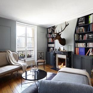 Réalisation d'un salon avec une bibliothèque ou un coin lecture bohème de taille moyenne et fermé avec un mur gris, une cheminée standard, aucun téléviseur et un sol en bois brun.