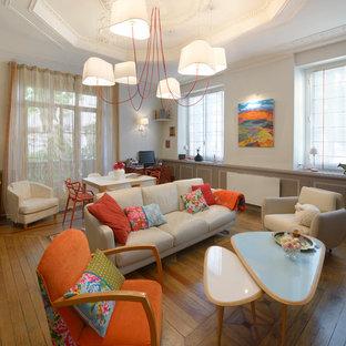Cette image montre un grand salon bohème ouvert avec un mur blanc, un sol en bois brun, aucune cheminée, aucun téléviseur et une salle de réception.
