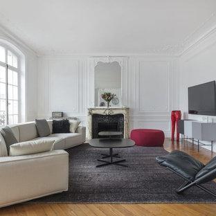 Inspiration pour un salon design avec un mur blanc, un sol en bois brun, une cheminée standard et un téléviseur fixé au mur.