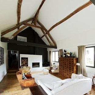 パリの大きいインダストリアルスタイルのおしゃれなLDK (白い壁、淡色無垢フローリング、標準型暖炉、コンクリートの暖炉まわり、茶色い床) の写真