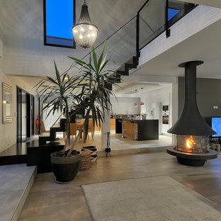 Esempio di un grande soggiorno design aperto con pareti bianche, parquet chiaro, camino sospeso e TV a parete