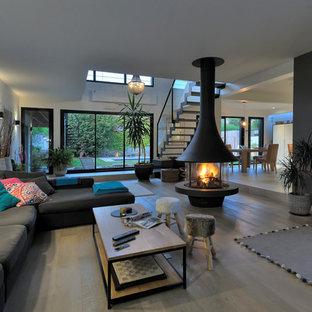 Réalisation d'un grand salon design ouvert avec un mur blanc, un sol en bois clair, cheminée suspendue, un téléviseur fixé au mur, un manteau de cheminée en métal et un sol beige.