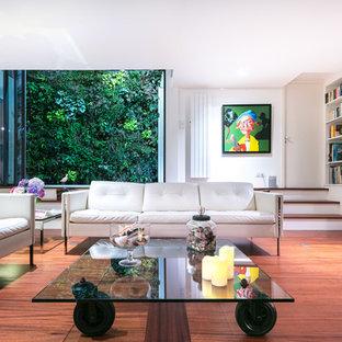 Cette image montre un salon avec une bibliothèque ou un coin lecture design avec un mur blanc, un sol en bois brun et un sol marron.