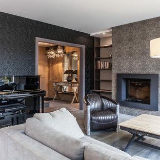 Idée de décoration pour un salon avec une bibliothèque ou un coin lecture tradition de taille moyenne et fermé avec un mur noir, un sol en bois clair, aucune cheminée et aucun téléviseur.