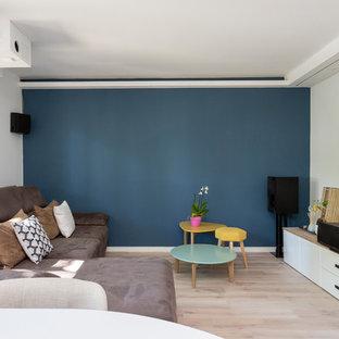Создайте стильный интерьер: открытая гостиная комната среднего размера в стиле модернизм с светлым паркетным полом, телевизором на стене, бежевым полом и синими стенами без камина - последний тренд