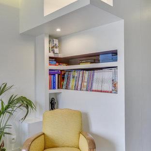 Ejemplo de biblioteca en casa abierta, minimalista, de tamaño medio, con paredes púrpuras, suelo de madera en tonos medios, televisor colgado en la pared y suelo marrón