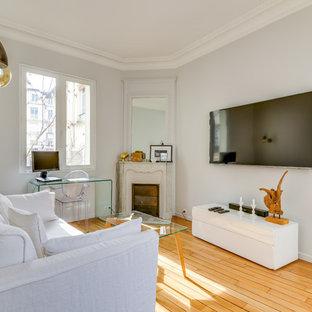 Cette image montre un salon design de taille moyenne et fermé avec un mur blanc, un sol en bois clair, une cheminée d'angle, un manteau de cheminée en pierre, un téléviseur fixé au mur et un sol marron.