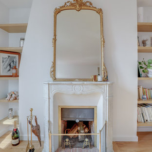 Design ideas for a small traditional open concept living room in Paris with a library, beige walls, marble floors, a standard fireplace, a stone fireplace surround, no tv and white floor.
