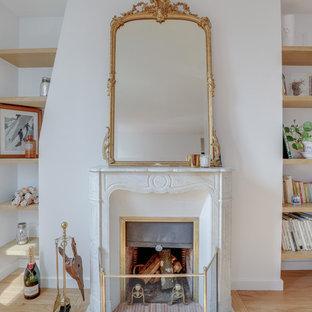 パリの小さいトラディショナルスタイルのおしゃれなLDK (ライブラリー、ベージュの壁、大理石の床、標準型暖炉、石材の暖炉まわり、テレビなし、白い床) の写真